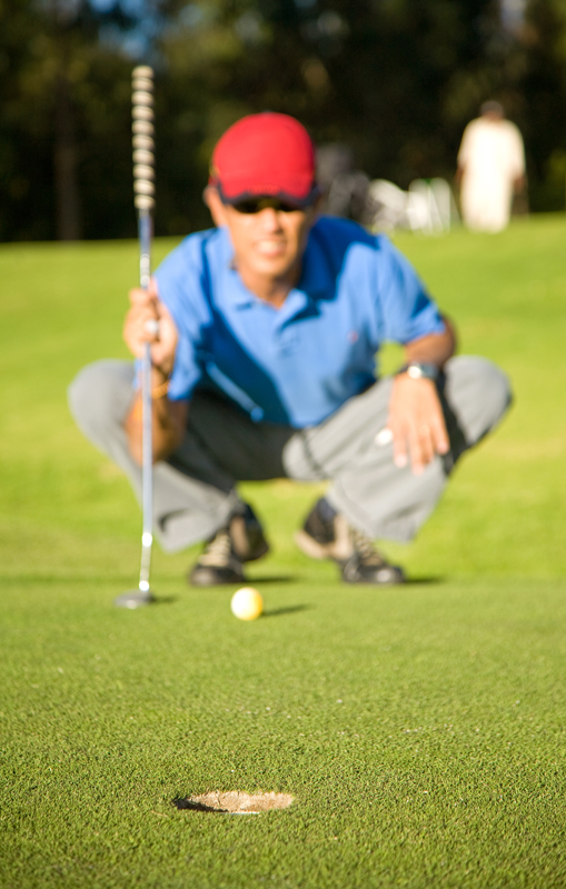 A young male golfer focuses on his putting and plans his golf practice plan